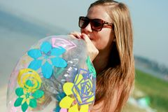 Happy young woman inflating the inflatable ball. Against blue sky Royalty Free Stock Photo