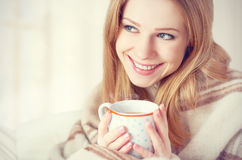 Happy Young Woman Is   Under A Blanket And  Cup Of Coffee On Winter Morning At Home