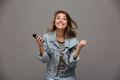 Happy young woman in jeans jacket clenching her fists in winner. Gesture, looking at camera,  over gray background Royalty Free Stock Photography