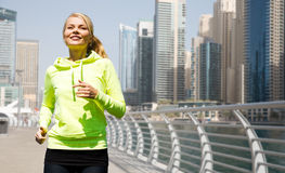 Happy young woman jogging outdoors Stock Photography