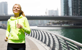 Happy young woman jogging outdoors Royalty Free Stock Images