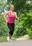 Happy young woman jogging outdoors Stock Images