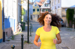 Happy young woman jogging through town Stock Photography