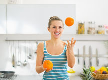 Happy young woman joggling with oranges in kitchen Stock Photos