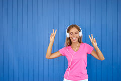 Happy young woman. Joy and music. Colorful portrait of happy young woman with white earphones is dancing against blue wall Royalty Free Stock Images
