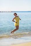 Happy young woman jump on the beach of sea Royalty Free Stock Photography
