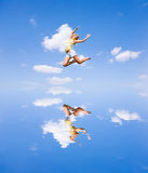 Happy young woman is jumping. Against the backdrop of blue sky Royalty Free Stock Photo