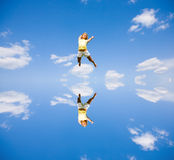 Happy young woman is jumping. Against the backdrop of blue sky. Reflected in the water Royalty Free Stock Images
