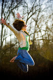 Happy Young Woman Jumping. Young woman facing sunset jumping high royalty free stock photo
