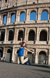 Happy young woman jumping against coliseum in Rome Stock Photos