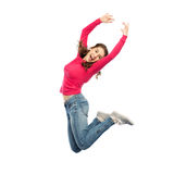 Happy young woman jumping in air or dancing. Happiness, freedom, motion and people concept - happy young woman jumping or dancing in air over white background Stock Photo