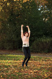 Happy young woman jumping in autumn park Stock Image