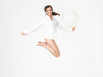 Happy young woman jumping with balloon Stock Photo