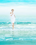 Happy young woman is jumping in the beach Royalty Free Stock Images