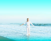 Happy young woman is jumping in the beach. Beauty, body Stock Photography