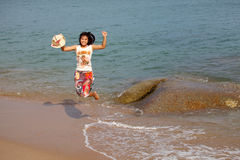 Happy young woman jumping on beach Royalty Free Stock Image