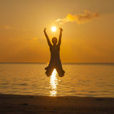 Happy young woman jumping on the beach.  Royalty Free Stock Photo