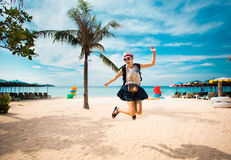 Happy young woman jumping on the beach. Near palm in funny hat royalty free stock photos