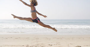 Happy Young Woman Jumping On The Beach Stock Photography