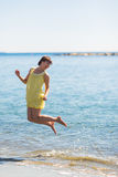 Happy young woman jumping on the beach of sea.  Royalty Free Stock Photography