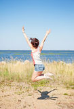 Happy young woman jumping on the beach Royalty Free Stock Photography
