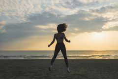 Happy young woman jumping on the beach on the sunrise background. royalty free stock photo