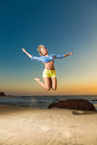 Happy young woman jumping on beach Royalty Free Stock Images