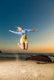 Happy young woman jumping on beach Stock Images