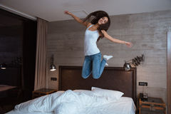 Happy young woman jumping on bed Stock Photos