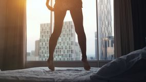 Happy young woman jumping on bed in luxury apartment at sunset time. lose up. Happy young woman jumping on bed in luxury apartment in royalty free stock photos