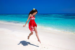 Happy young woman jumping on exotic sea, brunette smiling girl i Royalty Free Stock Images