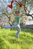 Happy young woman jumping on a field. With green grass and blooming trees stock image