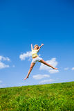 Happy young woman is jumping in a field.  Royalty Free Stock Images
