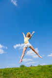 Happy young woman is jumping in a field. Against the backdrop of blue sky Stock Photo