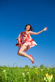 Happy young woman is jumping in a field Stock Photos