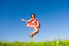 Happy young woman is jumping in a field Royalty Free Stock Photo