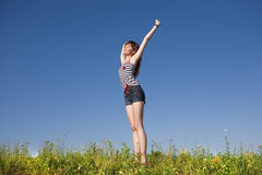 Happy young woman jumping in a field Stock Image