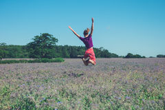 Happy young woman jumping in field of purple flowers. A happy young woman is jumping around in a field of purple flowers on a sunny summer day Stock Images