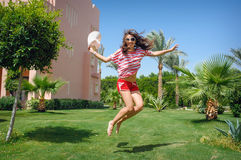 Happy Young Woman Jumping on the grass on rest Royalty Free Stock Images