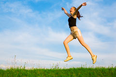 Happy young woman is jumping on green grass Royalty Free Stock Images