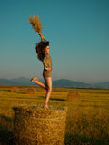 Happy, young woman jumping on hay stack Stock Images