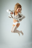 Happy young woman jumping high on gray background Stock Photos