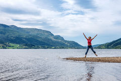 Happy young woman jumping for joy. Young woman on hiking travel excited and elated in Norway stock image