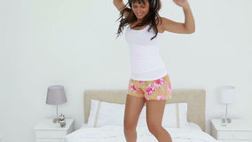 Happy young woman jumping while listening to music stock footage