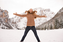 Happy young woman jumping outdoors among snow-capped mountains Royalty Free Stock Photos