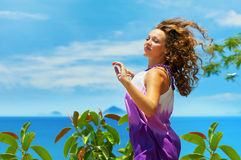 Happy young woman jumping over blue sky. Stock Images
