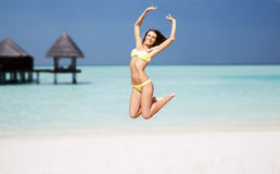 Happy young woman jumping over exotic beach Stock Images