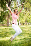 Happy young woman jumping in park Stock Photo