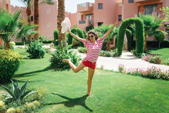 Happy young woman jumping in the park on the grass Royalty Free Stock Images