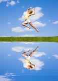 Happy young woman is jumping. Reflected in water. Against the backdrop of blue sky Royalty Free Stock Image